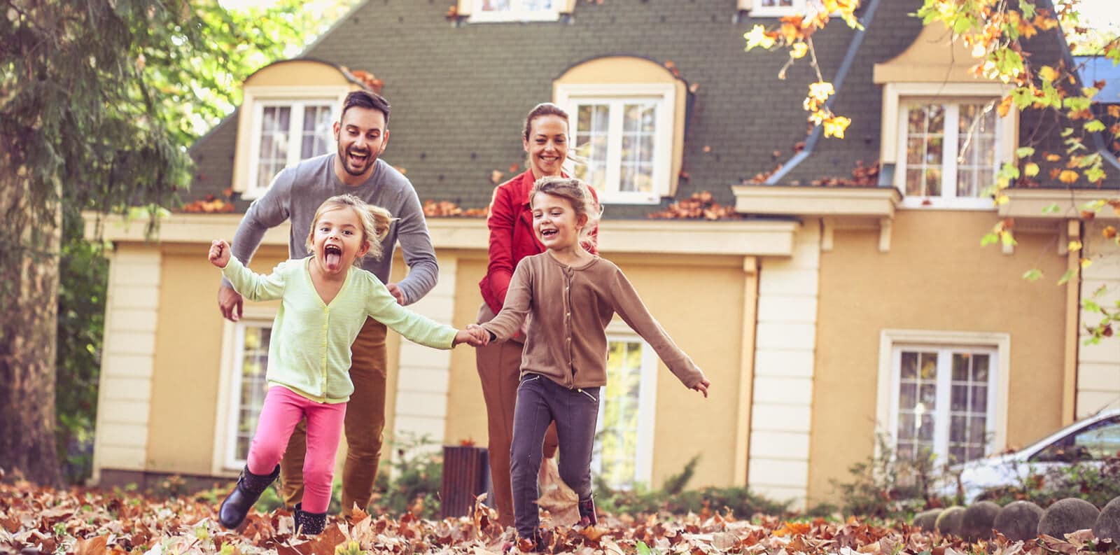 family enjoys a fall day outside their home